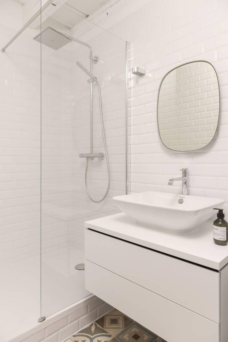 Un évier blanc assis sous un miroir - Salle de bains